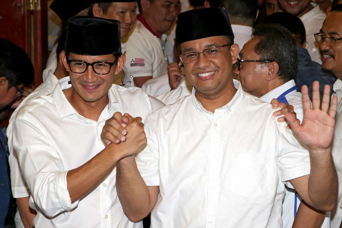 Jakarta governor candidate Anies Baswedan (right) celebrates with his running mate Sandiaga Uno after quick counts point to his victory.