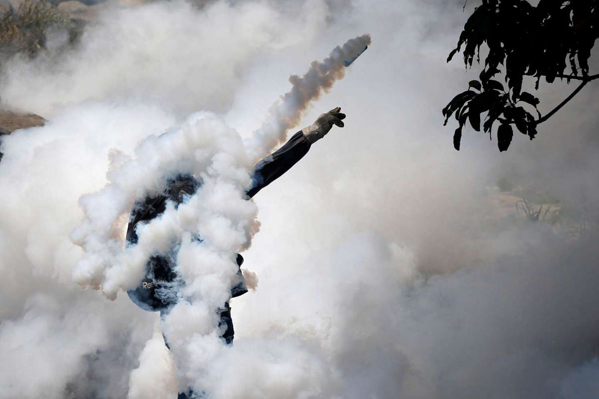 """A demonstrator throws back a tear gas grenade while clashing with riot police during the so-called """"mother of all marches"""" against Venezuela's President Nicolas Maduro in Caracas, Venezuela April 19, 2017. PHOTO: REUTERS"""