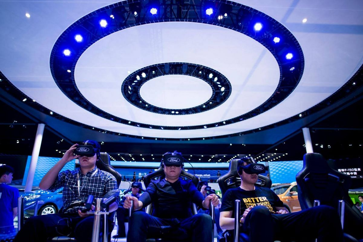 People try out virtual reality (VR) goggles at a stand for US carmaker Ford during the first day of the 17th Shanghai International Automobile Industry Exhibition in Shanghai on April 19, 2017.