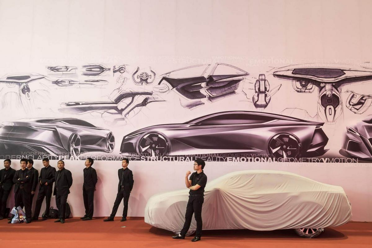 Security personnel stand next to a covered vehicle at the Shanghai Auto Show in Shanghai, China, on April 19, 2017.