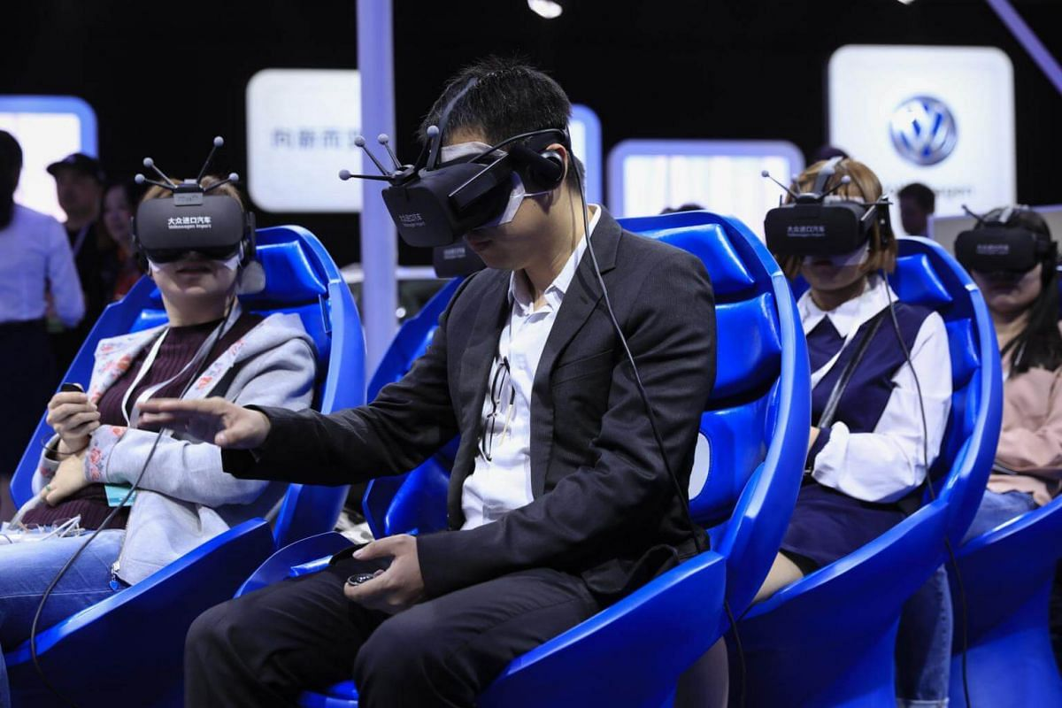 Visitors try out Virtual Reality (VR) headsets at Volkswagen's booth during the 17th Shanghai International Automobile Industry Exhibition in Shanghai, China, on April 19, 2017.
