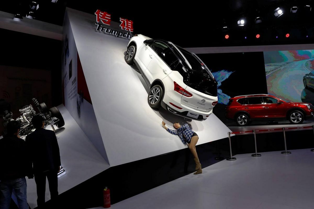 A woman takes pictures of the Trumpchi GS4 from GAC Group, displayed at the Shanghai Auto Show, in Shanghai, China, on April 20, 2017.