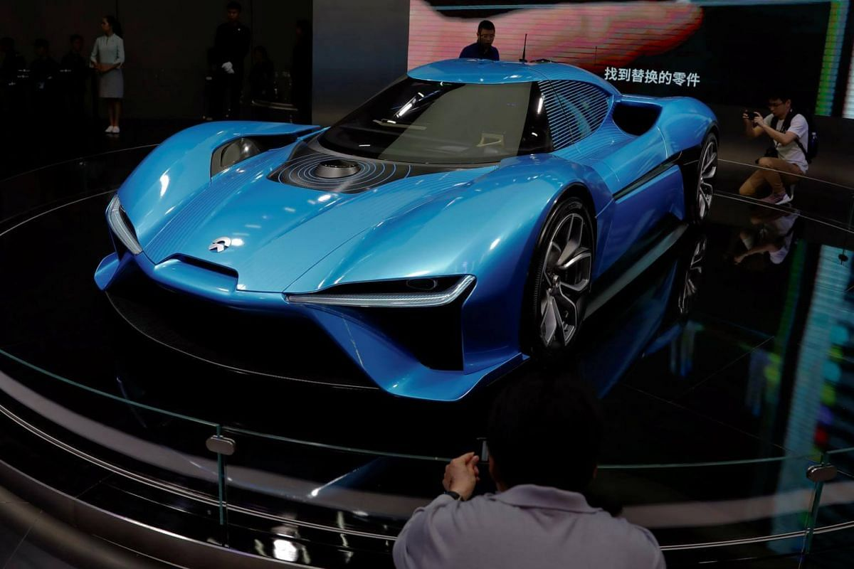 People gather around the NIO EP9 electric car displayed, at the Shanghai Auto Show, during media day, in Shanghai, China, on April 19, 2017.