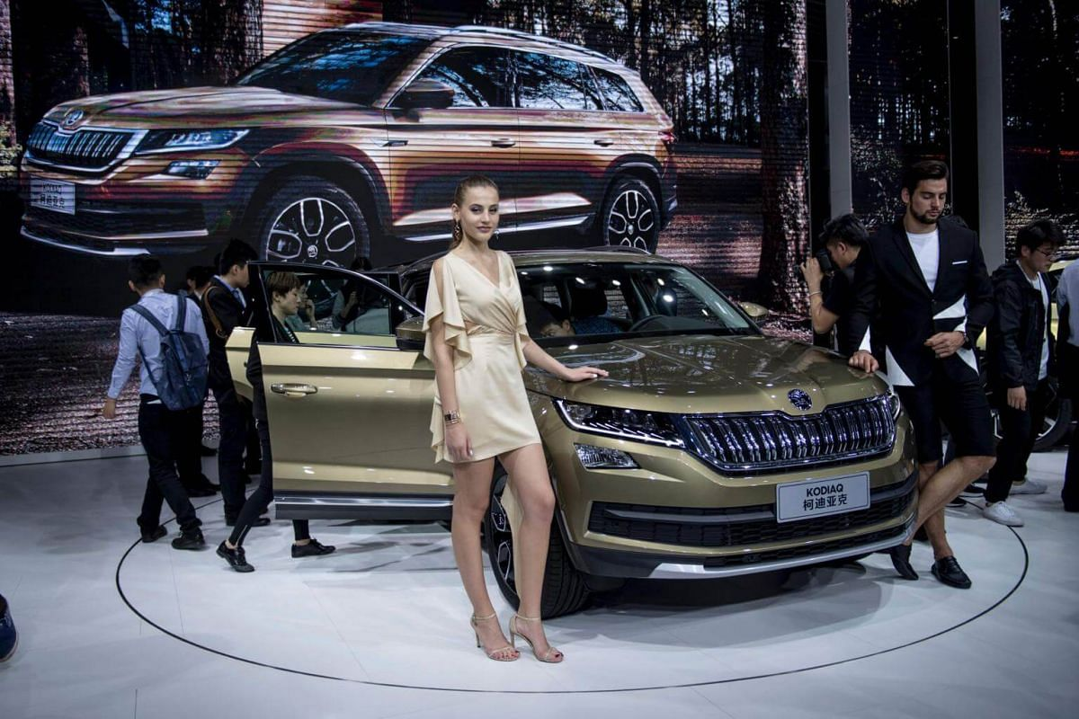 Models pose with a Skoda Kodiaq during media day at the 17th Shanghai International Automobile Industry Exhibition in Shanghai on April 19, 2017.