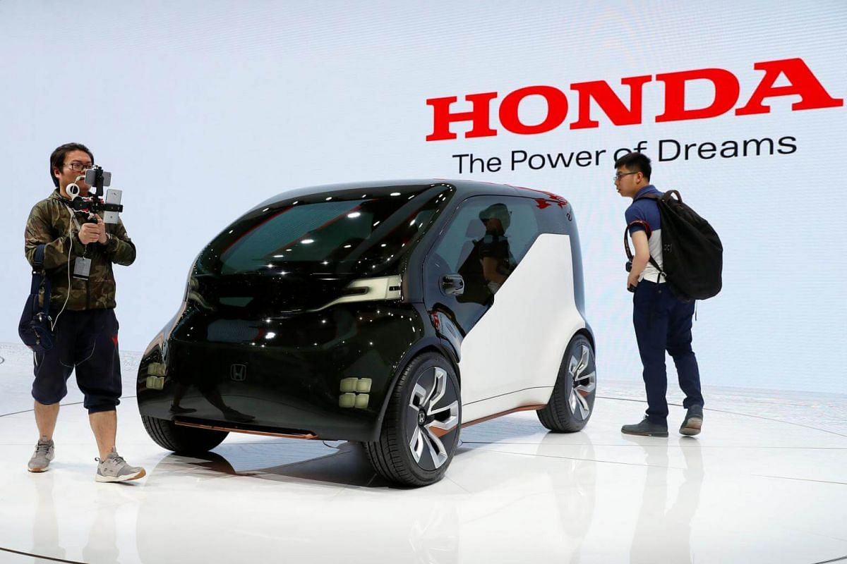 People gather around a Honda concept car displayed at Shanghai Auto Show on media day, in Shanghai, China, on April 19, 2017.
