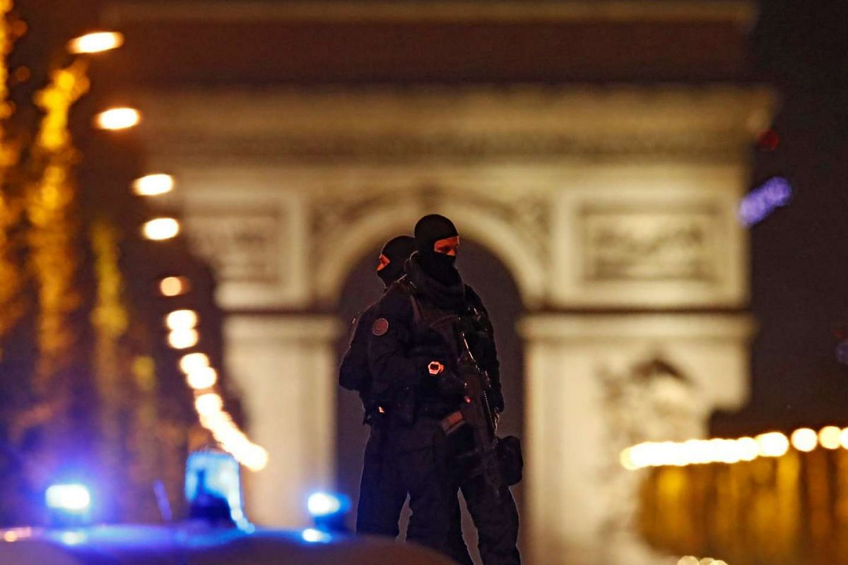 Masked police stand on top of their vehicle on the Champs Elysees Avenue after a policeman was killed and two others were wounded in a shooting incident in Paris, France, April 20, 2017. PHOTO: REUTERS