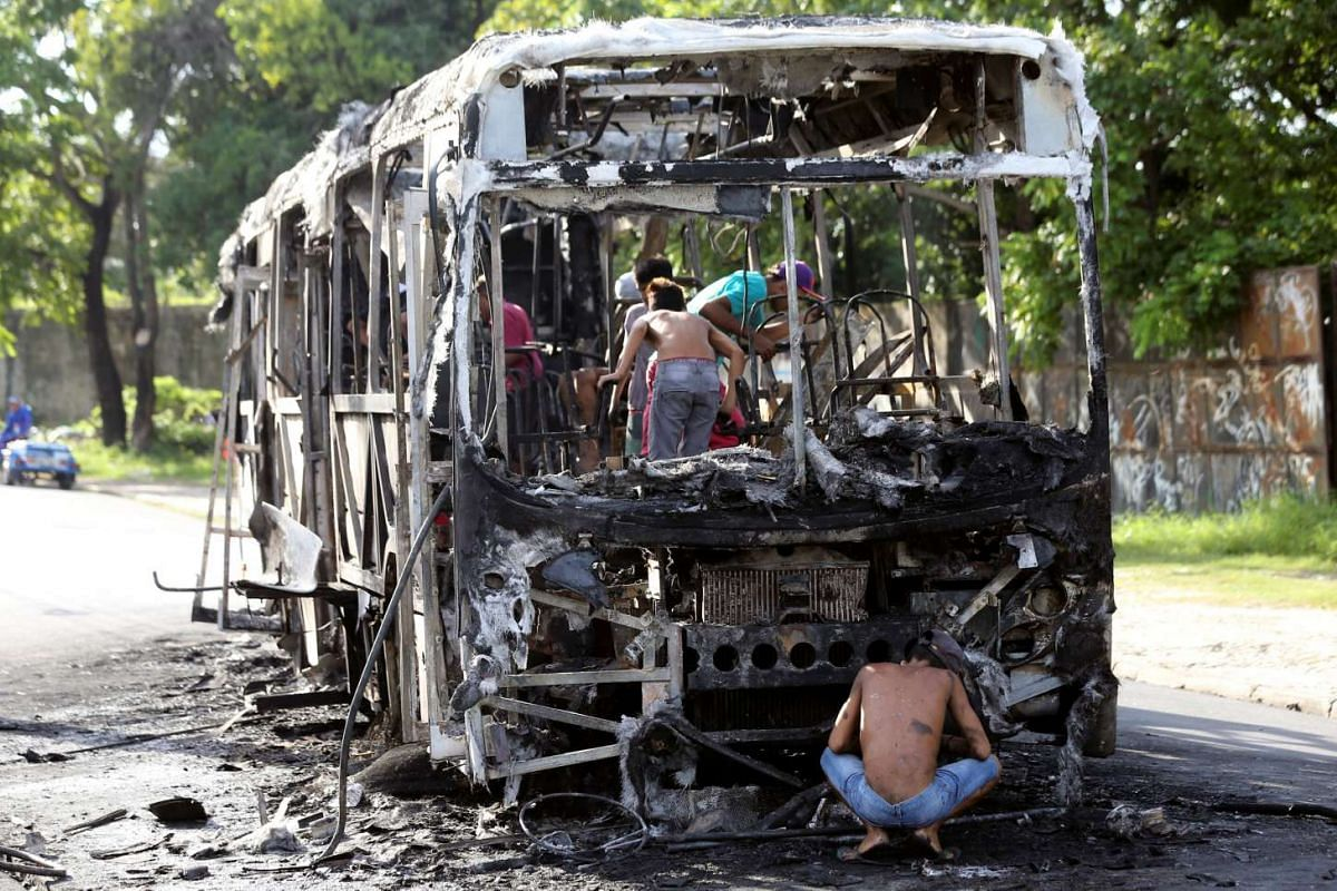People remove the remains of a burned bus in Fortaleza, Brazil, April 20, 2017. According to local media, approximately 20 buses were burned in the last two days in retaliation for the alleged transfers of prisoners held in the prisons of Fortaleza.