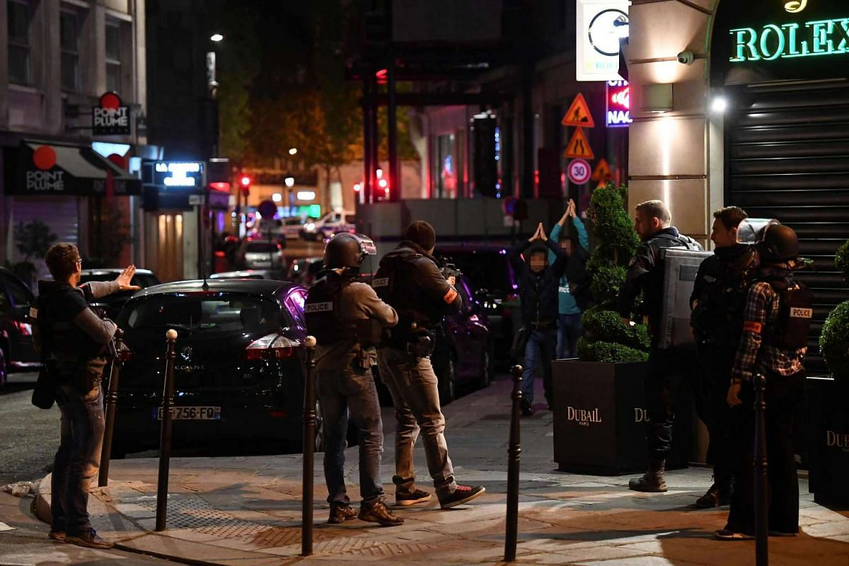 Police officers control passersby near the Champs Elysees in Paris after a shooting on April 20, 2017.