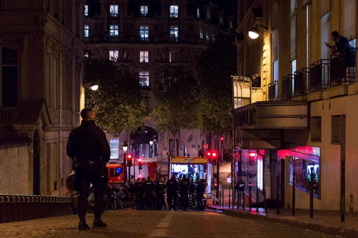 A police officer stands guard as firefighters wait near the site of a shooting at the Champs Elysees in Paris on April 20, 2017.