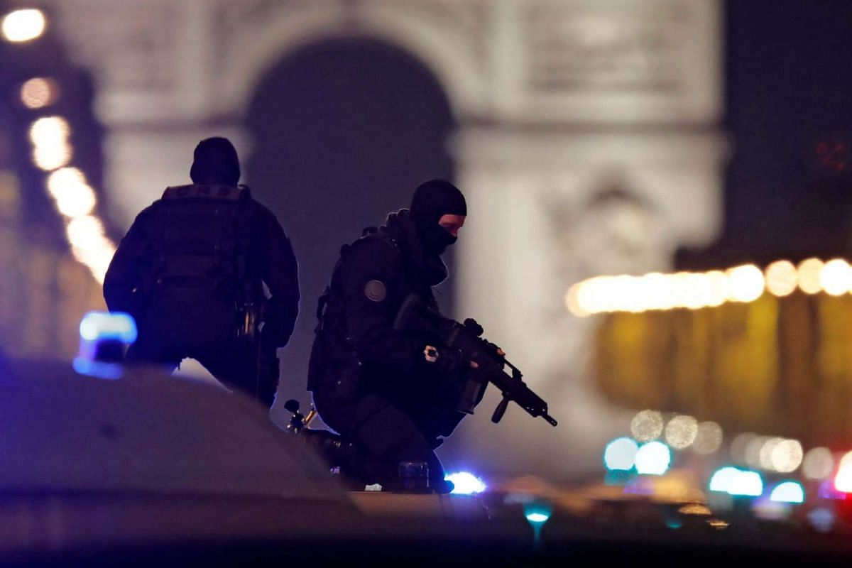 Masked police stand on top of their vehicle on the Champs Elysees Avenue after a policeman was killed and two others were wounded in a shooting incident in Paris, France, on April 20, 2017.