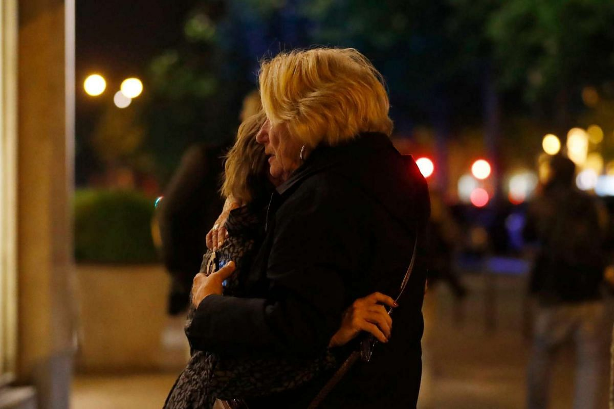 Two women hug each each other after a shooting in which two police officer were killed along with their attacker and another police officer wounded in a terror attack near the Champs Elysees in Paris, France, 20 April 2017.