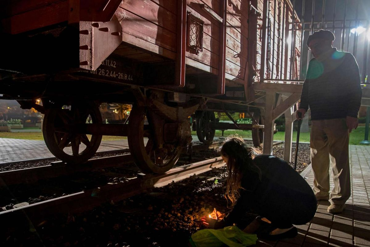 Chen and her 85-year-old grandfather Avraham, who is a Holocaust survivor, light candles next to a train wagon used in Nazi Germany to transport Jews to concentration camps, on April 23, 2017, in the Israeli coastal city of Netanya, on Holocaust Reme