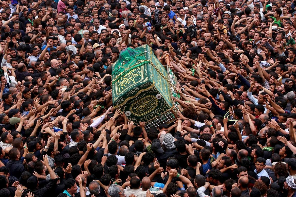 Iraqi Shiite Muslim worshipers carry the symbolic coffin of Imam Musa al-Kadhim during the funeral processions on the anniversary of his death by his shrine in Baghdad's northern district of Kadhimiya on April 23, 2017. PHOTO: AFP