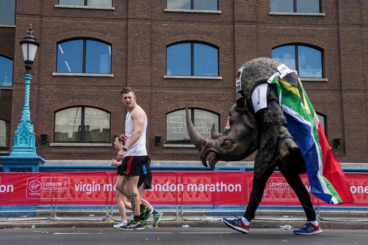 A runner dressed as a rhino crosses the half way point past a sign in a window reading '13 miles to prosecco' (CL), on Tower Bridge during the London Marathon in London on April 23, 2017. PHOTO: AFP