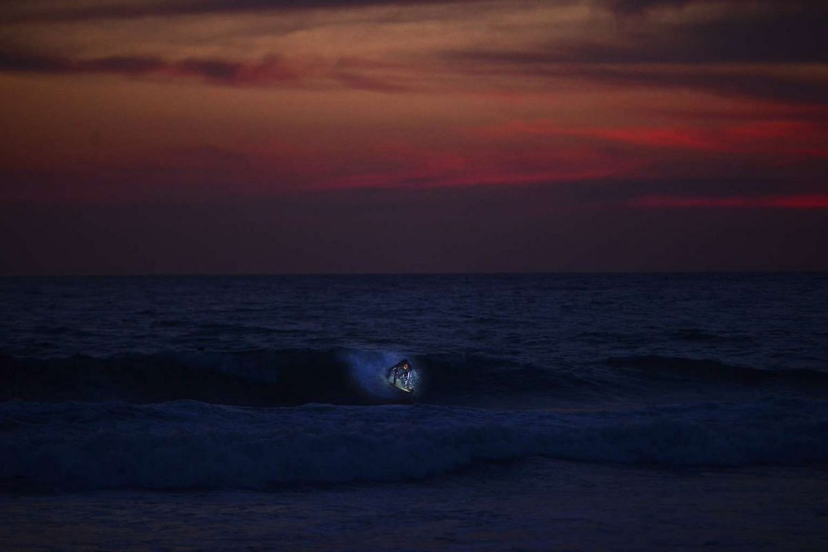 A photo released on April 24, 2017, shows Connor McDonald, of Ireland, surfing under a full moon near San Diego, April 10, 2017. McDonald is among a small subculture of surfers who dot coastlines from San Diego to Sydney after sunset, pursuing an adv