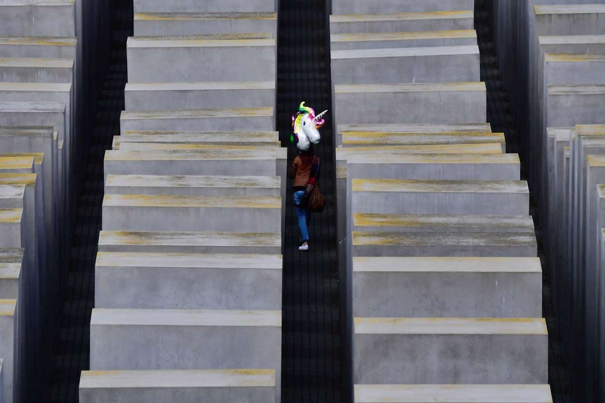 A visitor carrying a balloon shaped like a unicorn walks through Berlin's monument to the murdered Jews of Europe (Holocaust Memorial) on April 24, 2017. PHOTO: AFP