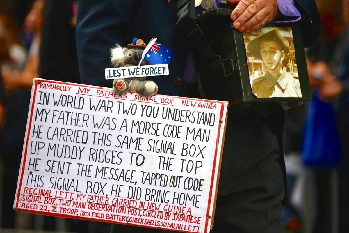 A relative of a veteran carries a sign and photograph as a tribute during the annual Anzac Day march through central Sydney, Australia, on April 25, 2017.