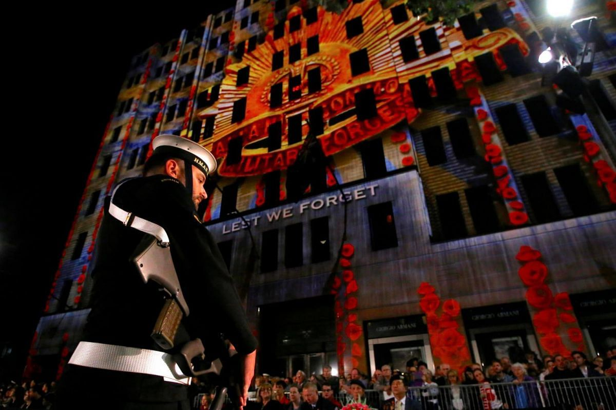 A member of the Australian Armed Forces and members of the public stand in front of a memorial message projected onto a building near the Cenotaph during the annual Anzac Day dawn service in Sydney, Australia, on April 25, 2017.