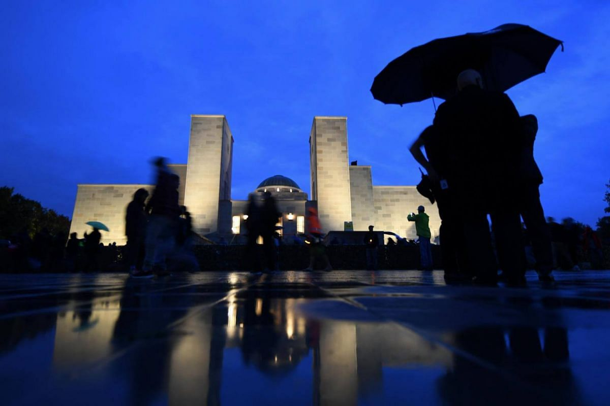 People walk past the Australian War Memorial at the end of the Anzac Day dawn service in Canberra, Australia, on 25 April 2017.