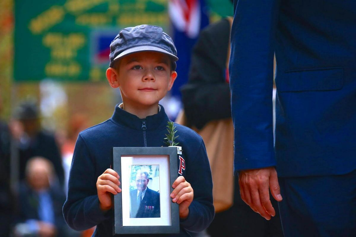 A relative of a veteran carries a photograph as a tribute during the annual Anzac Day march through central Sydney, Australia, on April 25, 2017.