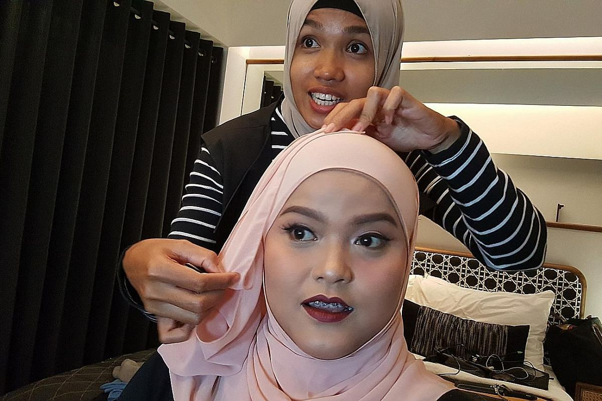 Freelance make-up artist Astri Viriana at a make-up and hijab-styling session with a client. The Go-Glam platform has helped her build up her business and customer base, while allowing her to spend more time with her family. A Go-Jek rider (centre) m
