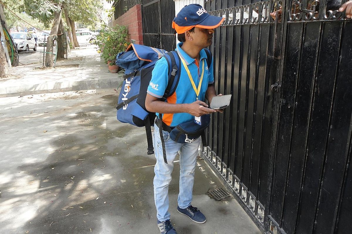 A happy Flipkart customer takes delivery of her package in Bengaluru, India. Deliverymen are the one human element in e-commerce transactions, as firms try to woo customers with the best buyer experience. E-commerce is booming in India, with more tha