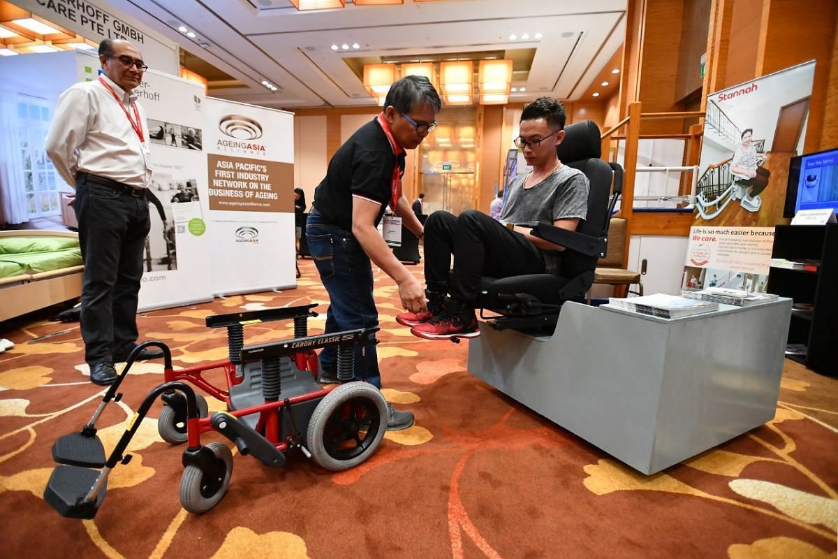 Mr Wah Shi Hao (sitting) and Mr Jose Maasin demonstrating the use of the improved version of the Autoadapt, which facilitates the transfer of person from a wheelchair to a car, at the exhibit showcase in the 8th International Ageing Asia Innovation F