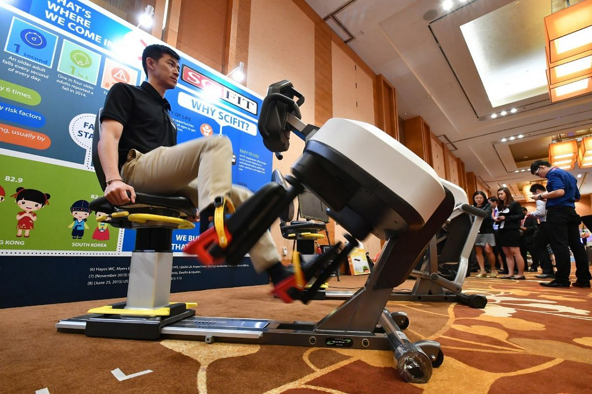 Mr Donavan Tan demonstrating the use of the Scifit Latitude Lateral Trainer, which helps to improve lateral stability and fall prevention for elderly, deconditioned people and people recovering from surgery, at the exhibit showcase in the 8th Interna