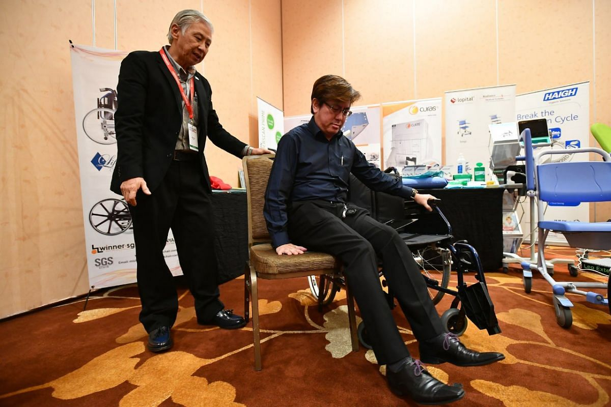 Mr Michael Pang and Mr Steven Ho, (sitting) demonstrating the use of the world's first remote-control transfer wheelchair, at the exhibit showcase in the 8th International Ageing Asia Innovation Forum 2017 (AAIF2017) at Marina Bay Sands Convention Ce