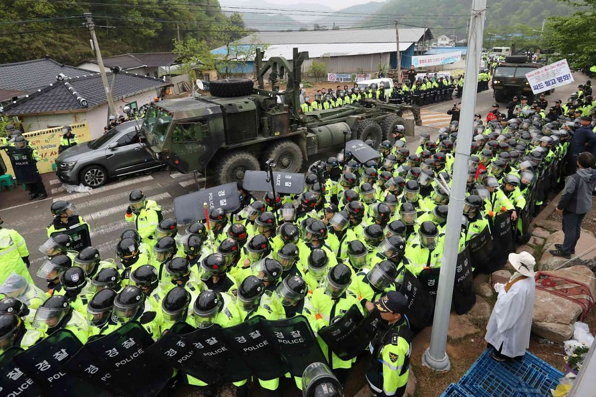 Protesters and police stand by as trailers carrying US THAAD missile defence equipment enter a deployment site in Seongju, early on April 26, 2017. Arrival of the six trailers at the golf course location sparked clashes between locals and police, the