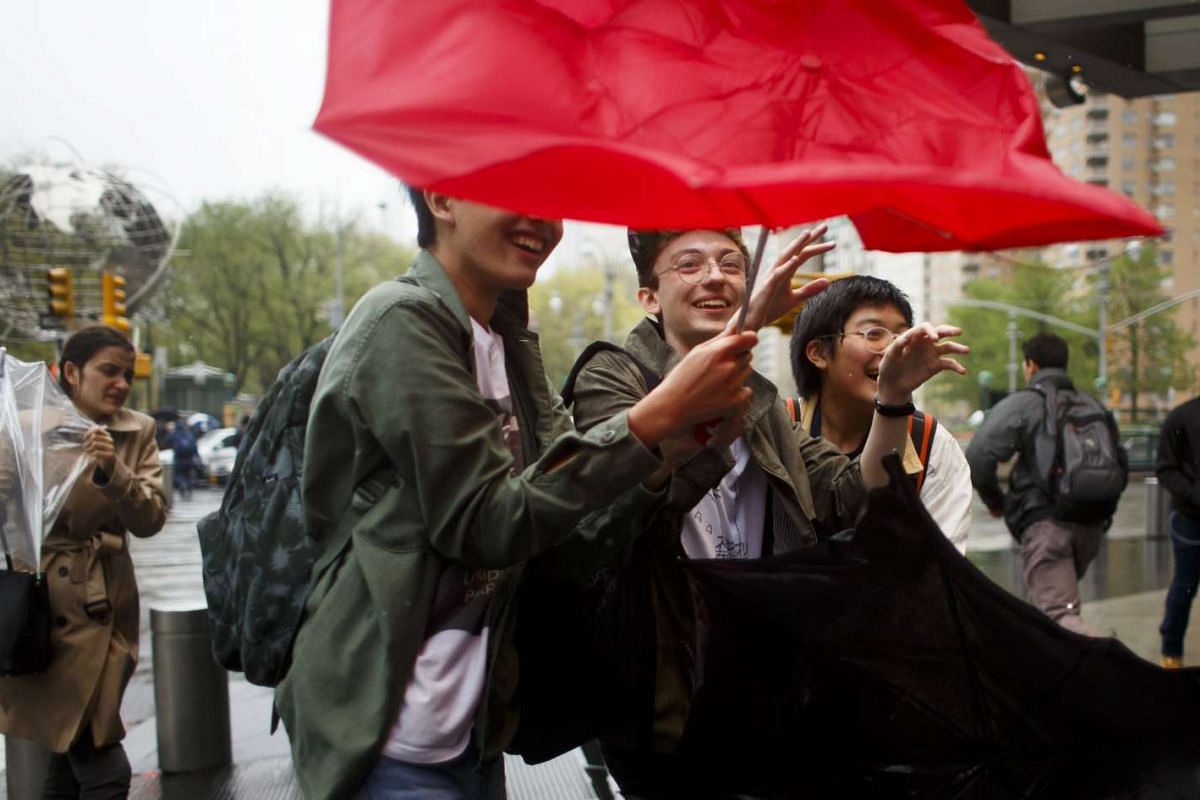 People try to hold on to their umbrellas in a heavy wind blowing through Columbus Circle in New York, New York, USA, April 25, 2017. PHOTO: EPA