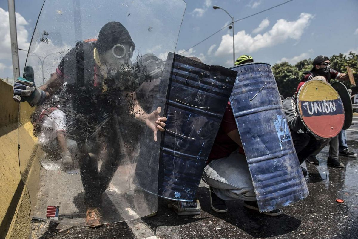 Opposition activists clash with riot police during a protest against President Nicolas Maduro in Caracas on April 26, 2017. PHOTO: AFP