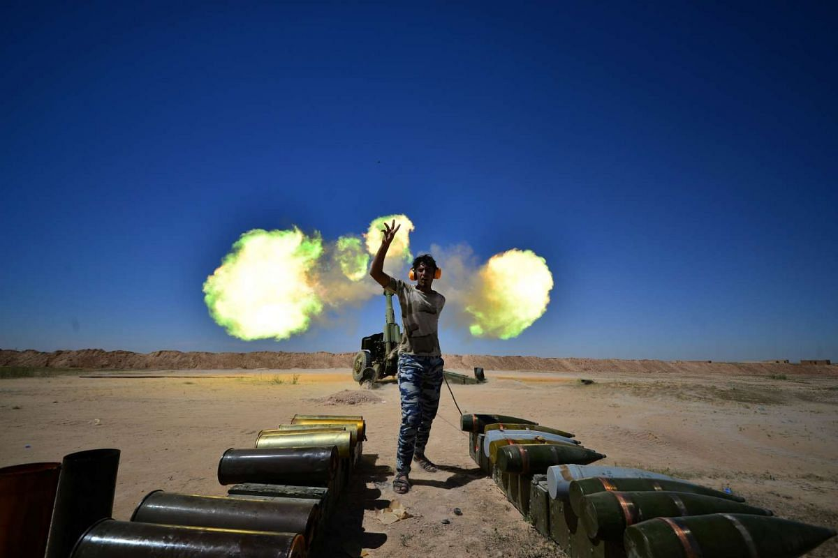 Iraqi paramilitary troops fire towards Islamic State militants during a battle with Islamic State militants on the outskirts of the ancient city of Hatra near Mosul,Iraq April 26, 2017. PHOTO: REUTERS