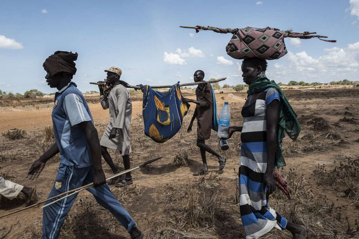 Relatives escort a Dinka woman affected by malaria to a temporary hospital in Mingkaman, a camp for the Internally displaced people (IDPs) on April 26, 2017, in the Eastern Lakes States. PHOTO: AFP