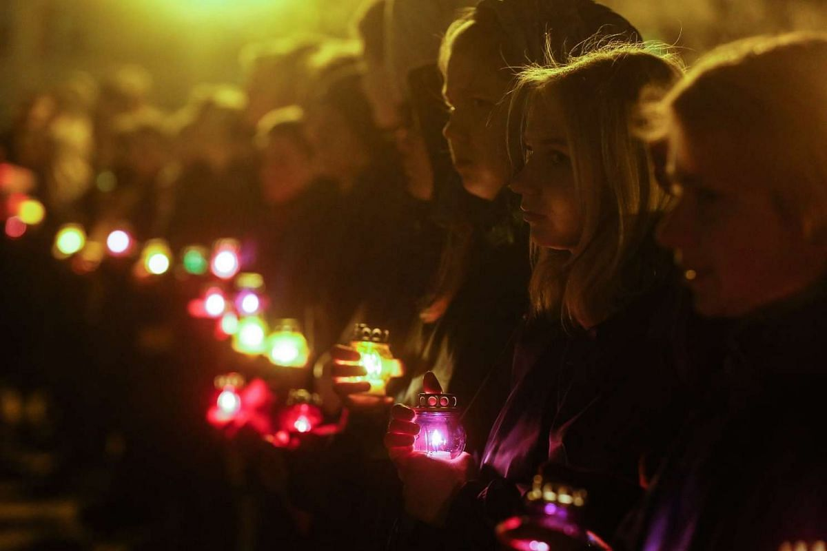 Young Ukrainians hold candles during a mourning ceremony near of the memorial for 'liquidators' who died during cleaning up works after the Chernobyl nuclear power plant disaster, in Slavutich city, some 190 km north of the capital Kiev, Ukraine, ear