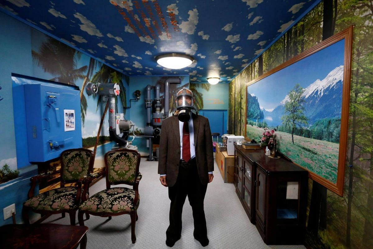 Mr Seiichiro Nishimoto wearing a gas mask in a model room for his company's nuclear shelters. Bright blue skies are painted on the shelter's ceiling and the wallpaper depicts palm tree-lined beach.