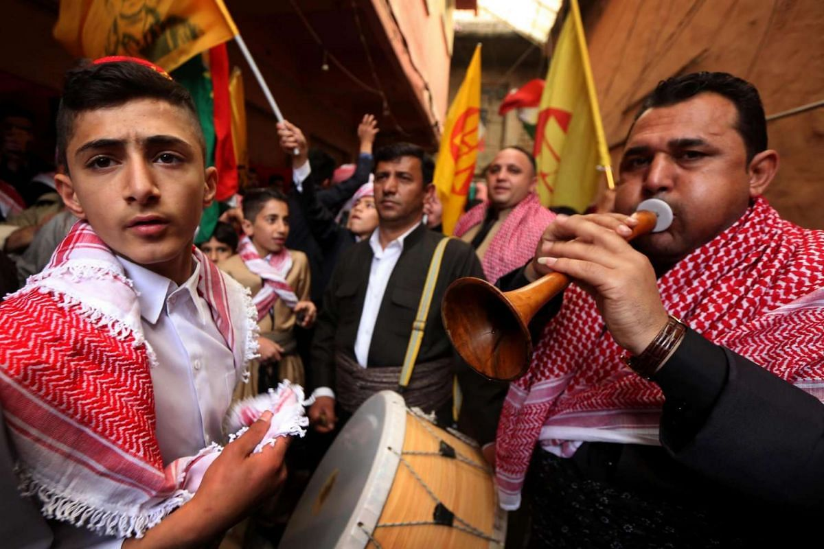 Iraqi Kurds play music as they walk through the town of Akra, 500km north of Baghdad, on March 20,  as they celebrate the Noruz spring festival.  The Persian New Year is an ancient Zoroastrian tradition celebrated by Iranians and Kurds which coincid