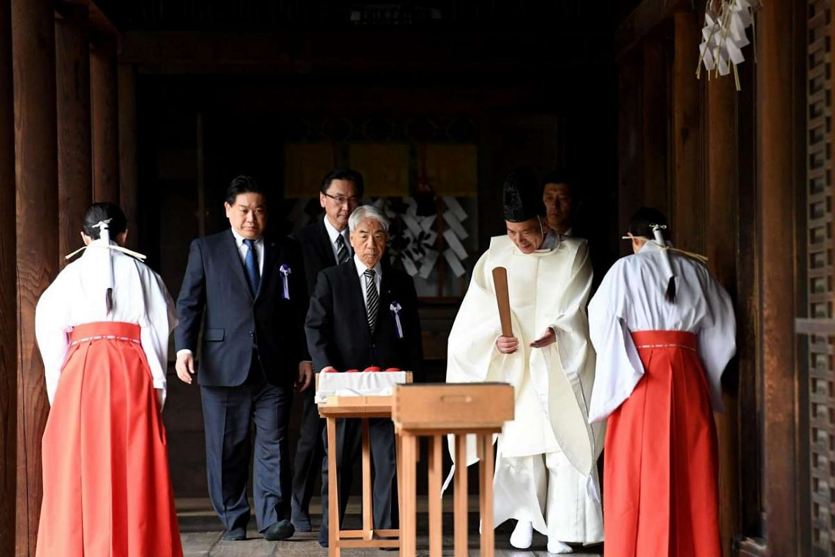A Shinto priest (second from the right) leading Japanese lawmakers to offer sake at the Yasukuni Shrine during the shrine's spring festival in Tokyo on April 21.