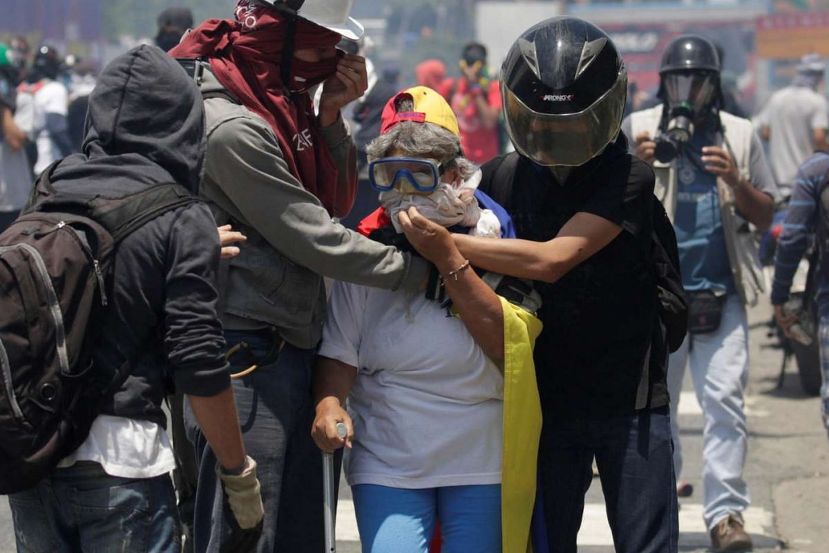 Opposition supporters offer aid to a resident in the midst of a rally against   President  Maduro in Caracas on April 26.