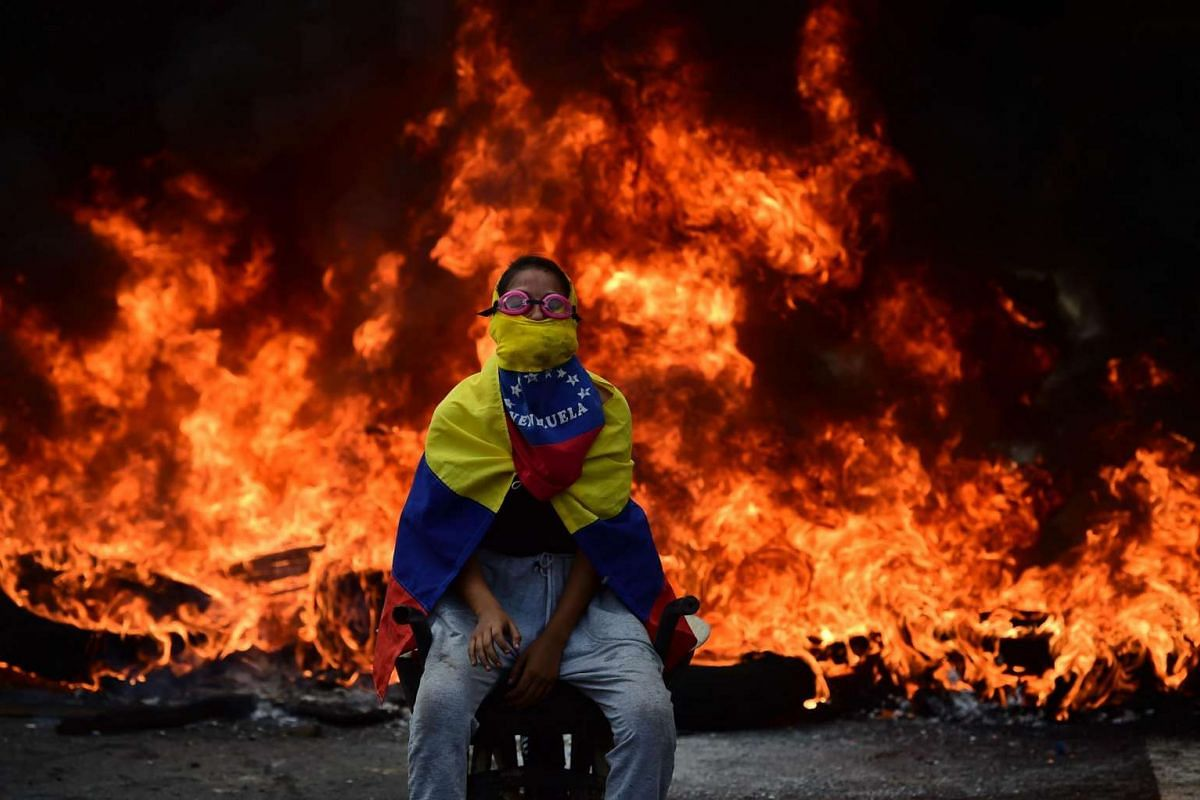 An activist is backdropped by a burning barricade during a demonstration against President Nicolas Maduro in Caracas, on April 24.