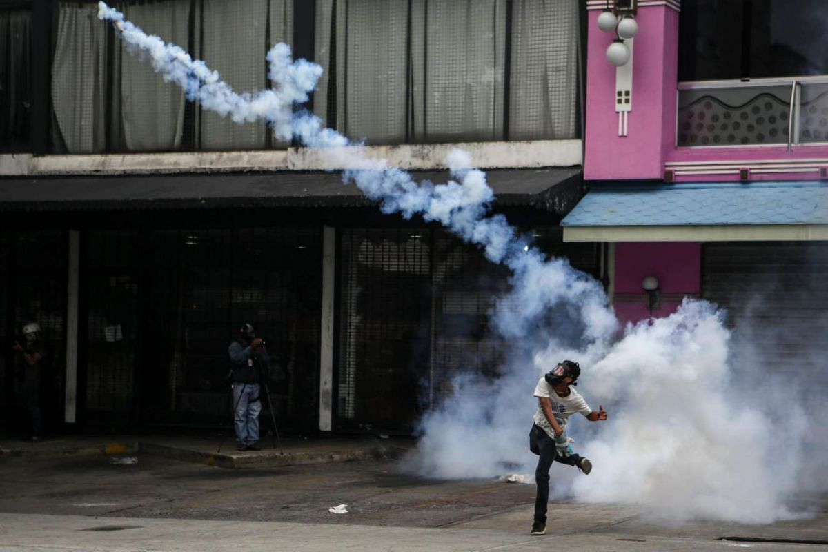 A masked protester hurling tear gas towards security forces.