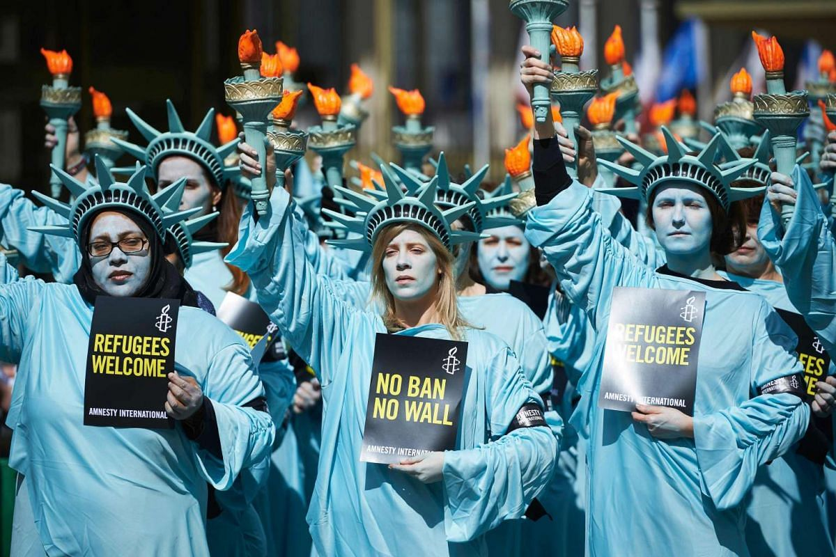 Activists from Amnesty dressed as the Statue of liberty take part in a demonstration to mark the first 100 days in office of US President Donald Trump outside the US Embassy in London on April 27, 2017. PHOTO: AFP