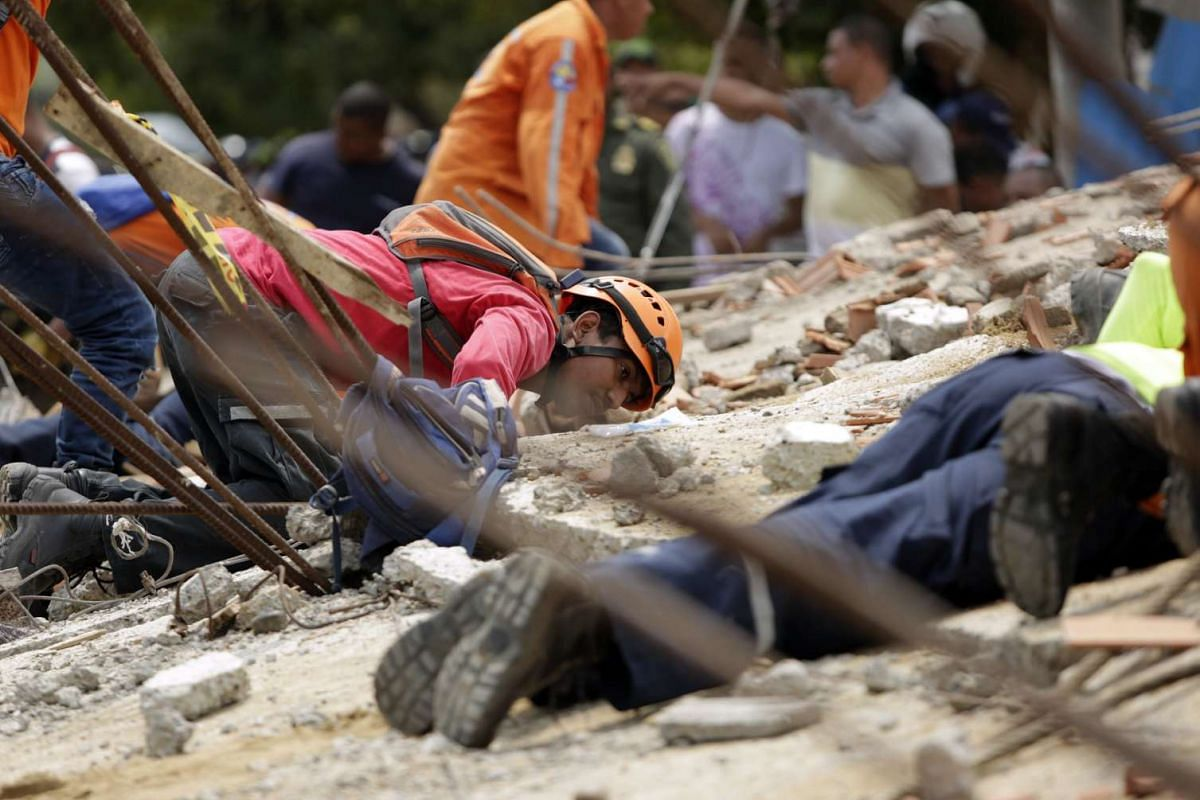 Colombian rescue workers look for survivors after the collapse of a building in Cartagena, north of Colombia, on April 27, 2017. At least 3 people died and other 8 were injured in the collapse of a six story building which was under construction in C