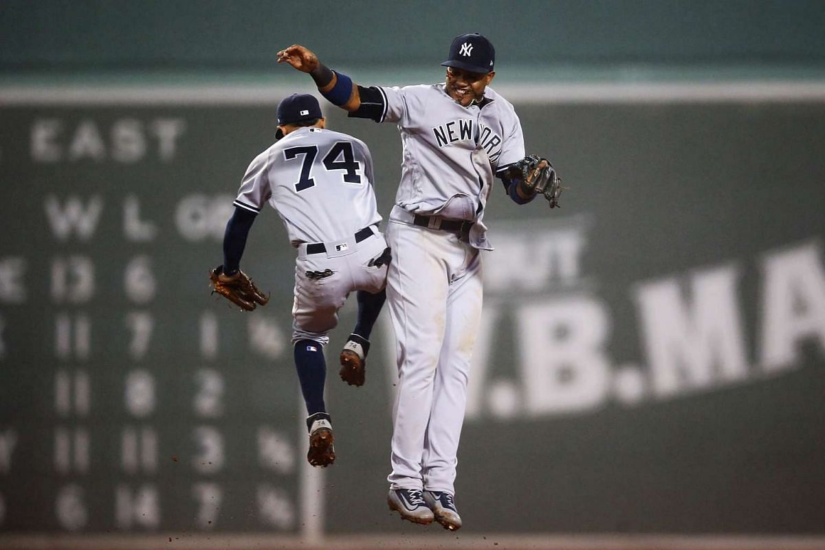 Aaron Judge #99 high fives Ronald Torreyes #74 of the New York Yankees after their victory over the Boston Red Sox at Fenway Park on April 26, 2017 in Boston, Massachusetts. PHOTO: GETTY IMAGES/AFP