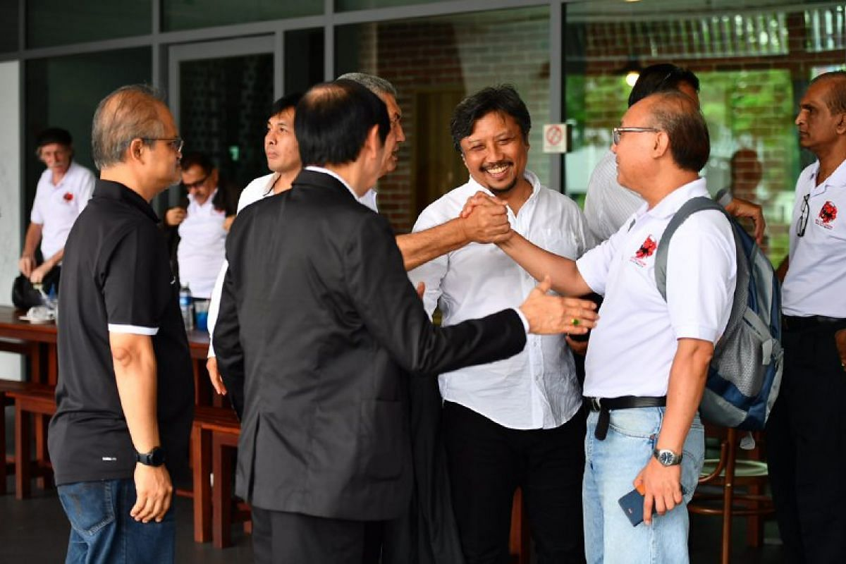 Team Game Changers members hugging and shaking hands at the end of their meeting at Ayam Penyet President restaurant at Kallang Wave Mall.