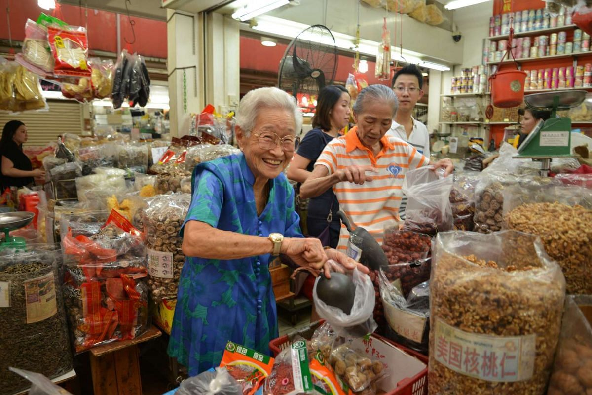 Madam Lim Swee Ee (above), 90, is happy keeping busy serving customers at a trading store at Albert Centre.