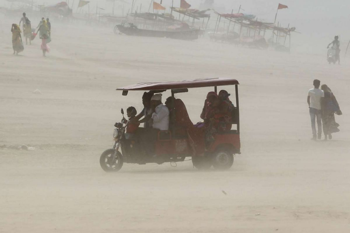 People travel in an auto rickshaw on the banks of the river Ganges during a dust storm in Allahabad, India May 1, 2017.