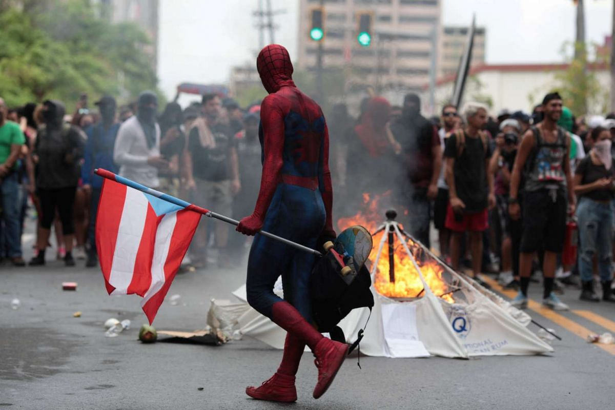 A man dressed in a superhero outfit walks past a burning barricade during a protest against the government's austerity measures as Puerto Rico faces a deadline on Monday to restructure its $70 billion debt load or open itself up to lawsuits from cred