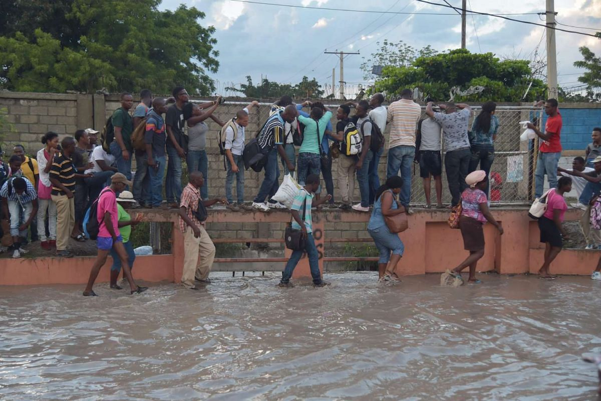 People walk in a partially flooded street after rain in the Haitian capital Port-au-Prince on May 2, 2017.