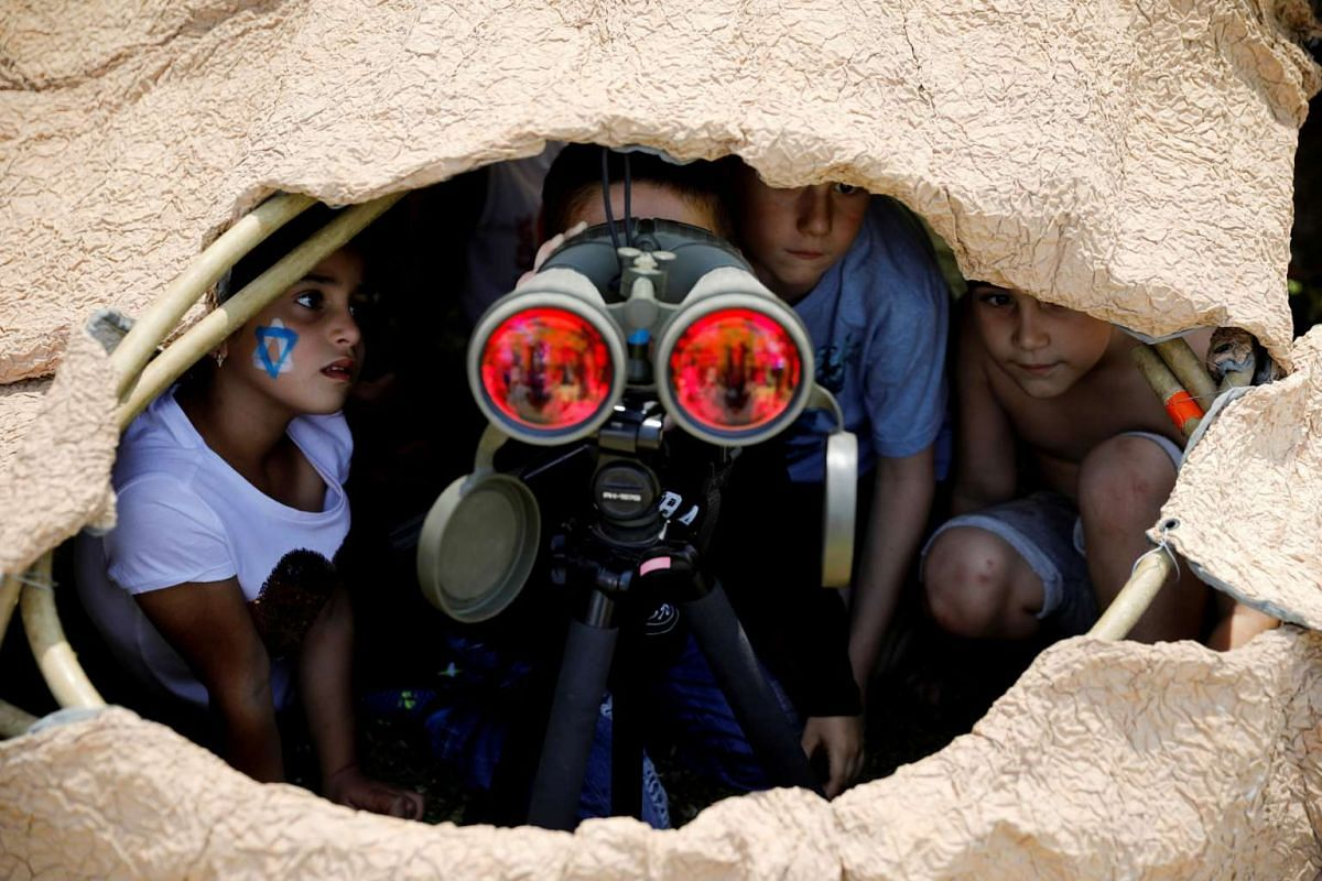 Israeli children look through binoculars during a display of Israeli Defence Forces equipment and abilities, as part of the celebrations for Israel's Independence Day marking the 69th anniversary, in the southern city of Sderot on May 2, 2017